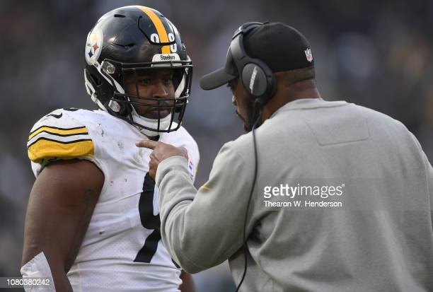 Head coach Mike Tomlin of the Pittsburgh Steelers talks with his player Vince Williams on the sidelines against the Oakland Raiders during an NFL...
