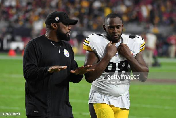 Head coach Mike Tomlin of the Pittsburgh Steelers talks with Vince Williams while walking to the locker room after the end of the first half of a...