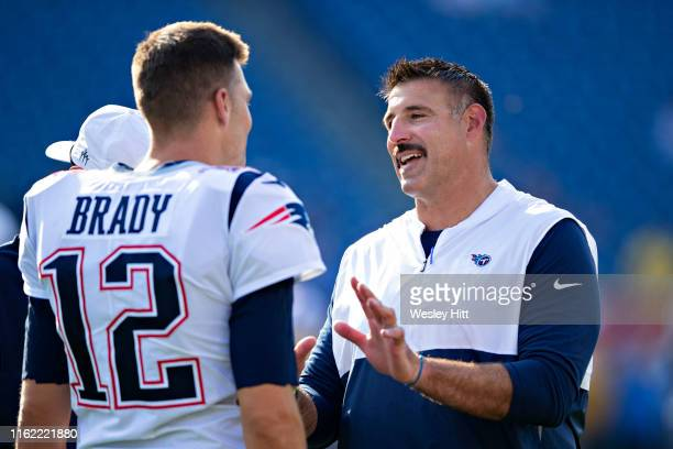 Head Coach Mike Vrabel of the Tennessee Titans talks with Tom Brady of the New England Patriots before a week two preseason game at Nissan Stadium on...