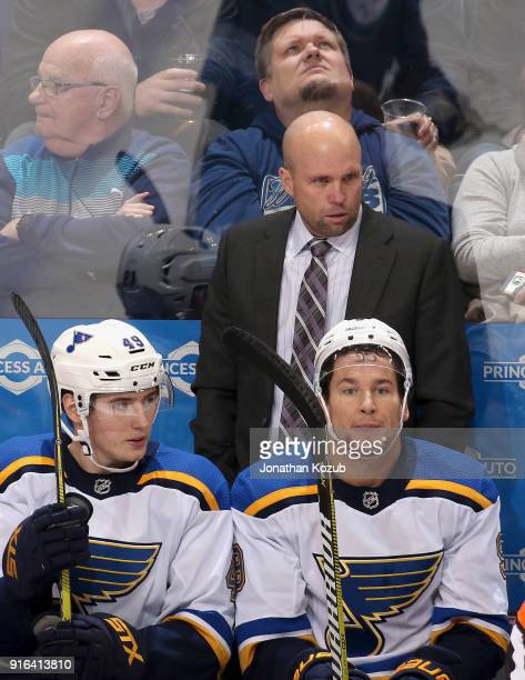 Head Coach Mike Yeo Ivan Barbashev and Scottie Upshall of the St Louis Blues look on from the bench during third period action against the Winnipeg...