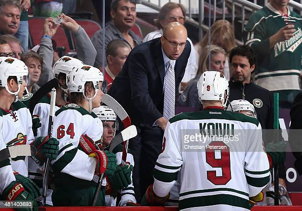 Head coach Mike Yeo of the Minnesota Wild talks with Mikko Koivu during a break from the NHL game against the Phoenix Coyotes at Jobingcom Arena on...