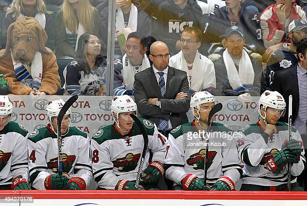 Head Coach Mike Yeo of the Minnesota Wild watches third period action against the Winnipeg Jets from the bench at the MTS Centre on October 25 2015...
