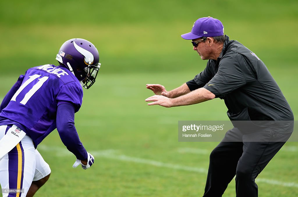 Head coach Mike Zimmer of the Minnesota Vikings blocks Mike Wallace #11 during a drill at practice on June 4, 2015 at Winter Park in Eden Prairie, Minnesota.
