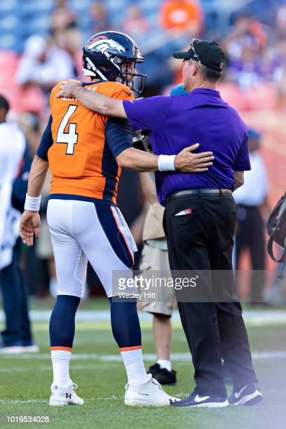 Head Coach Mike Zimmer of the Minnesota Vikings hugs Case Keenum of the Denver Broncos before a game during week one of preseason at Broncos Stadium...