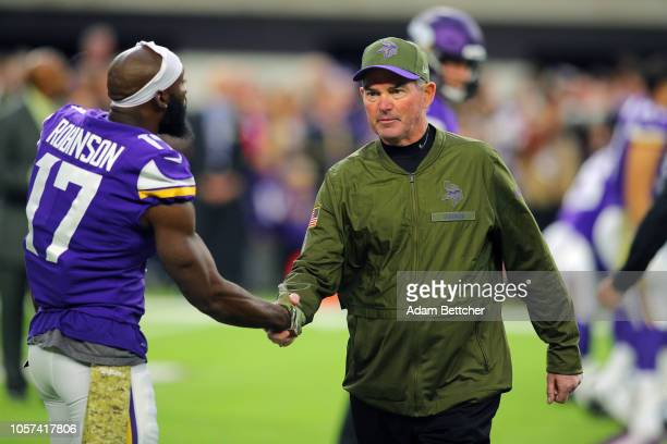 Head coach Mike Zimmer of the Minnesota Vikings shakes hands with Aldrick Robinson of the Minnesota Vikings during the pregame against the Detroit...