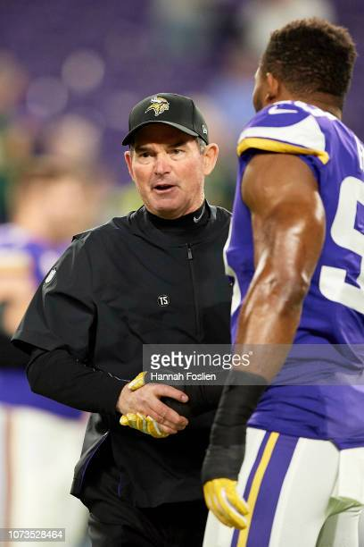 Head coach Mike Zimmer of the Minnesota Vikings shakes hands with Danielle Hunter before the game against the Green Bay Packers at US Bank Stadium on...