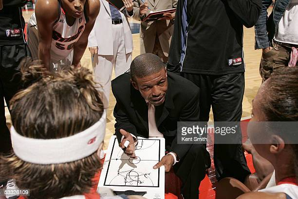 Head coach Muggsy Bogues of the Charlotte Sting tells his players the new plays during the game against the Sacramento Monarchs on August 4 2005 at...