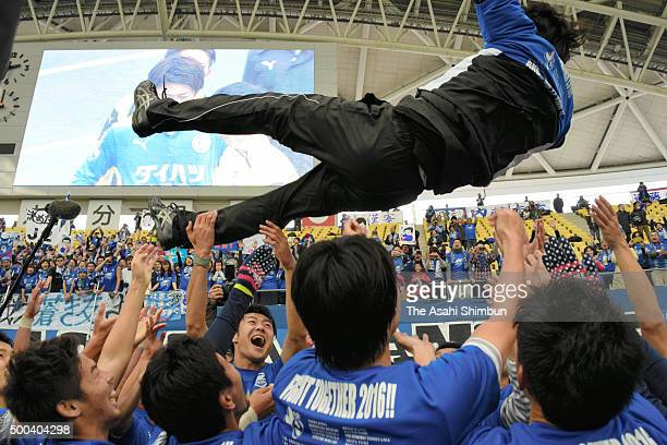 Head coach Naoki Soma of Machida Zelvia is thrown into the air after his team's promotion to J2 after the JLeague J2/J3 PlayOff second leg match...