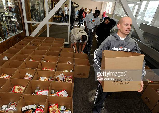 Head coach Nate Bjorkgren of the Bakersfield Jam helps carry out a Thanksgiving dinner box during the Bakersfield Jam Thanksgiving Box Give Away...