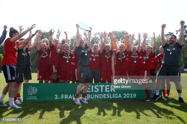 Head coach Nathalie Bischof and players of Muenchen celebrate with the trophy after winning the title after the 2 Frauen Bundesliga match between TSG...
