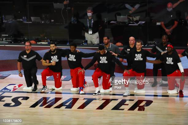 Head coach Nick Nurse of the Toronto Raptors and players kneel for the national anthem before action against the Brooklyn Nets in game four of the...