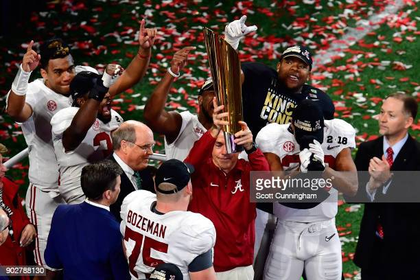 Head coach Nick Saban of the Alabama Crimson Tide holds the trophy while celebrating with his team after defeating the Georgia Bulldogs in overtime...