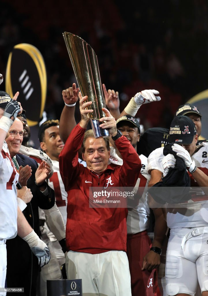Head coach Nick Saban of the Alabama Crimson Tide holds the trophy while celebrating with his team after defeating the Georgia Bulldogs in overtime to win the CFP National Championship presented by AT&T at Mercedes-Benz Stadium on January 8, 2018 in Atlanta, Georgia.