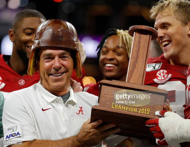 Head coach Nick Saban of the Alabama Crimson Tide laughs after his players put the Old Leather Helmet on his head after their 42-3 win over the Duke...