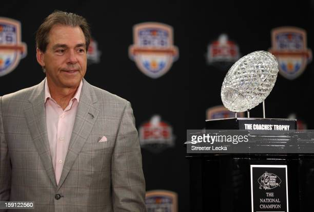 Head coach Nick Saban of the Alabama Crimson Tide looks at the National Championship trophy during the Discover BCS National Championship Press...