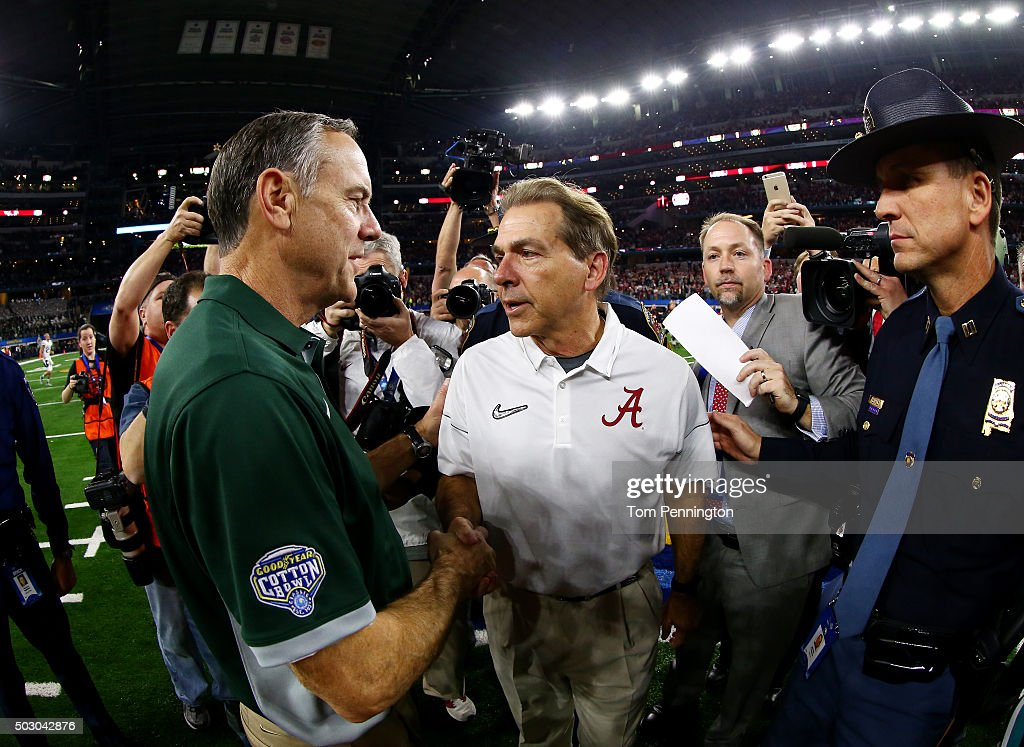 Head coach Nick Saban (R) of the Alabama Crimson Tide shakes hands with head coach Mark Dantonio of the Michigan State Spartans after the Crimson Tide defeated the Spartans 38 to 0 in the Goodyear Cotton Bowl at AT&T Stadium on December 31, 2015 in Arlington, Texas.