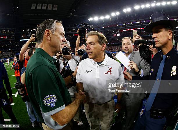 Head coach Nick Saban of the Alabama Crimson Tide shakes hands with head coach Mark Dantonio of the Michigan State Spartans after the Crimson Tide...