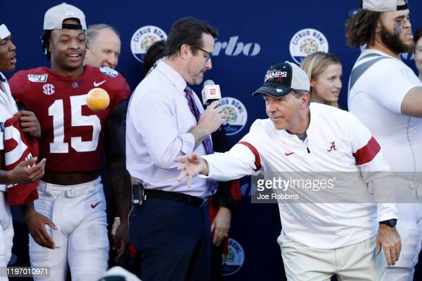 Head coach Nick Saban of the Alabama Crimson Tide tosses oranges to his players following a win against the Michigan Wolverines in the Vrbo Citrus...