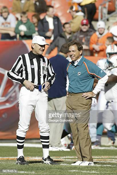 Head coach Nick Saban of the Miami Dolphins smiles while talking to referee Bernie Kukar before a game against the Cleveland Browns at Cleveland...