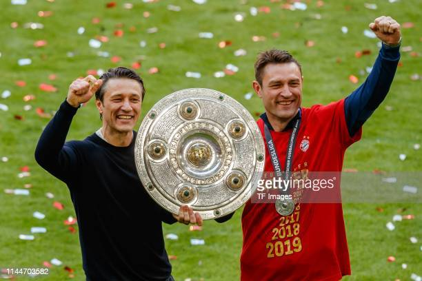 head coach Niko Kovac of FC Bayern Muenchen and assistant coach Robert Kovac of FC Bayern Muenchen celebrate with the championship trophy after the...