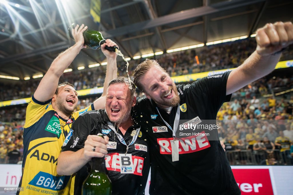 Head coach Nikolaj Jacobsen (C) and Manager Oliver Roggisch (R) of Rhein-Neckar Loewen are showered in champagne after the DKB HBL match between Rhein-Neckar Loewen and THW Kiel at SAP Arena on May 31, 2017 in Mannheim, Germany.