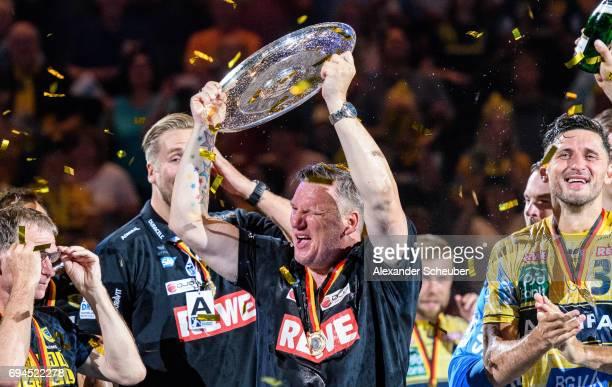 Head coach Nikolaj Jacobsen of Rhein Neckar Loewen and Alexander Petersson of Rhein Neckar Loewen celebrate the championship with the trophy during...