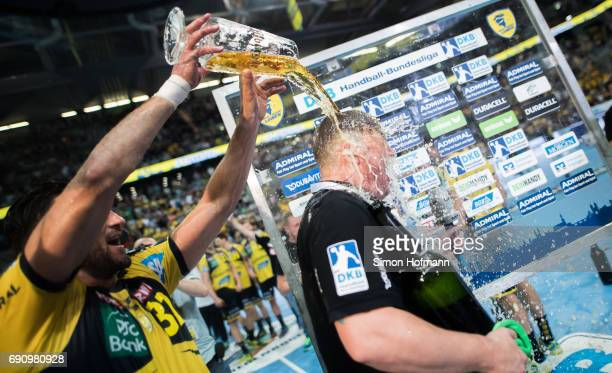 Head coach Nikolaj Jacobsen of RheinNeckar Loewen is showered in beer by Alexander Petersson after the DKB HBL match between RheinNeckar Loewen and...