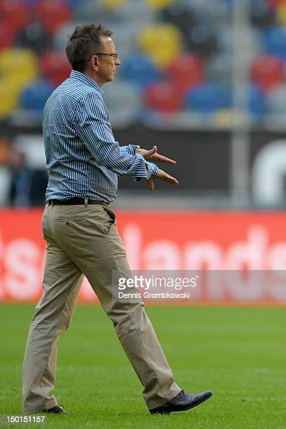 Head coach Norbert Meier of Duesseldorf signals the end of the game after referee Christian Fischer was attacked during the friendly match between...