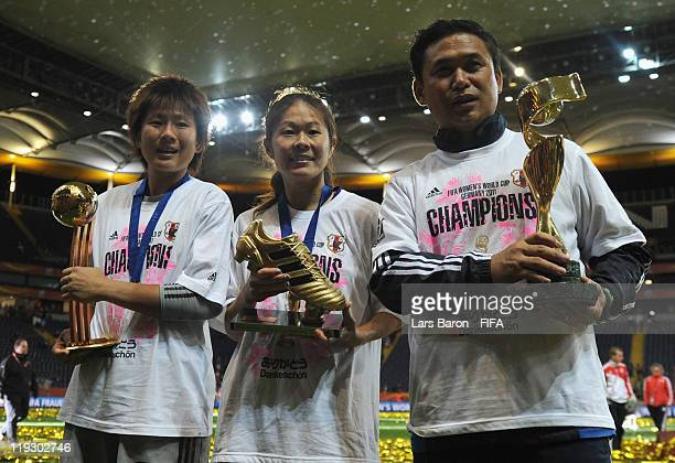 Head coach Norio Sasaki of Japan holds the trophy next to goalkeeper Ayumi Kaihori and Homare Sawa after winning the FIFA Women's World Cup Final...