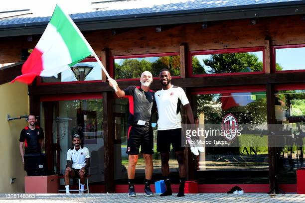 Head Coach of AC Milan Stefano Pioli and Fikayo Tomori wave the Italian flag during the AC Milan training session at Milanello on July 11, 2021 in...