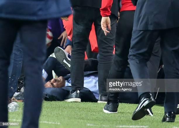 Head coach of Besiktas Senol Gunes is seen on the ground after fans threw a bottle to his head during Ziraat Turkish Cup Semi Final second leg soccer...