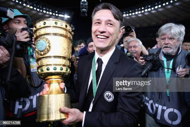 Head coach of Eintracht Frankfurt Niko Kovac caries the DFB Cup trophy after winning the DFB Cup final against Bayern Muenchen at Olympiastadion on...