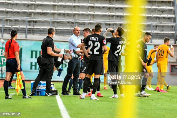 Head coach of FC Zorya Luhansk Viktor Skrypnyk and his charges are seen on the sideline during the Ukrainian Premier League Matchday 29 game against...