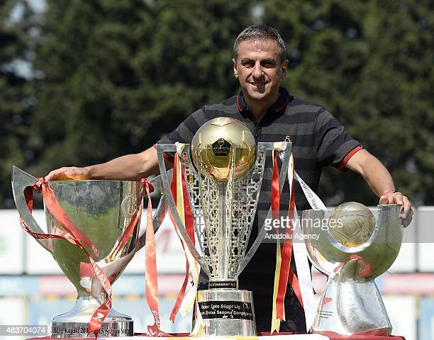 Head coach of Galatasaray Hamza Hamzaoglu poses with the 2014-2015 Turkish Cup, Turkish Spor Toto Super League and Turkish Super Cup trophies in...