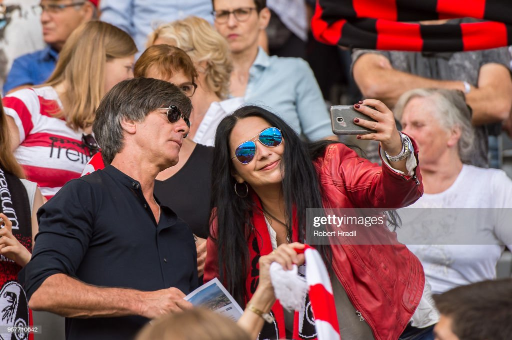 Head coach of Germany Joachim Loew takes a selfie with fan of Freiburg during the Bundesliga match between Sport-Club Freiburg and FC Augsburg at Schwarzwald-Stadion on May 12, 2018 in Freiburg im Breisgau, Germany.