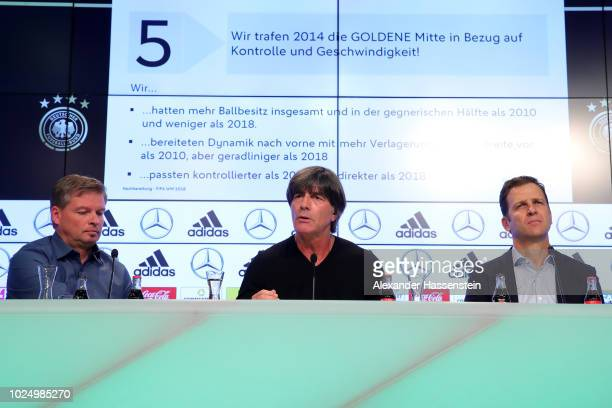 Head coach of Germany Joachim Loew talks to the media whilst press officer Jens Grittner and team manager Oliver Bierhoff look on at Allianz Arena on...