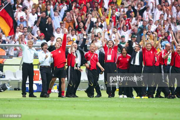 Head coach of Germany Jurgen Klinsmann assistant coach Joachim Low and goalkeeper trainer Andreas Kopke celebrates with the staff during the World...
