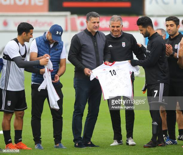 Head coach of Iran national football team Carlos Queiroz gives a jersey to former Iranian football player Ali Daei during the team's training session...
