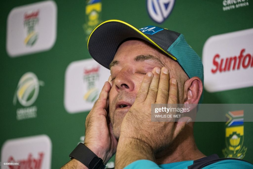 TOPSHOT - Head Coach of the Australia cricket team Darren Lehmann wipes his eyes during a press conference in Johannesburg on March 29, 2018 at which he announced his resignation after the forthcoming Test match against South Africa. Australia cricket coach Darren Lehmann said on March 29, 2018 he would quit after the final match of the scandal-tainted Test series in South Africa after the team's former captain Steve Smith broke down in tears and accepted complete responsibility for the ball-tampering incident. /