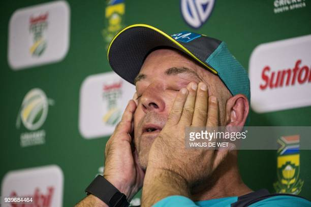 TOPSHOT Head Coach of the Australia cricket team Darren Lehmann wipes his eyes during a press conference in Johannesburg on March 29 2018 at which he...