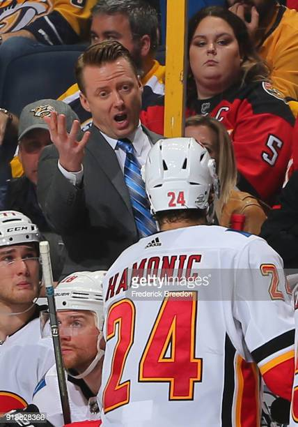 Head coach of the Calgary Flames Glen Gulutzan speaks to Travis Hamonic during a timeout against of the Nashville Predators during the third period...
