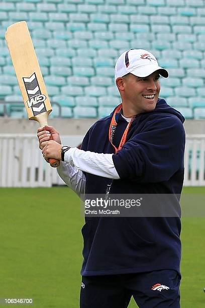 Head coach of the Denver Broncos Josh McDaniels jokes around while playing cricket prior to the start of a team training session at The Brit Oval on...