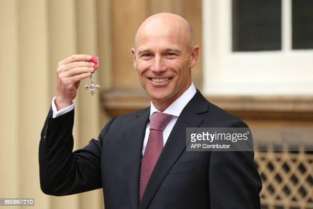 Head Coach of the England and Great Britain women's hockey teams Danny Kerry poses with his MBE medal after being appointed a Member of the Order of...