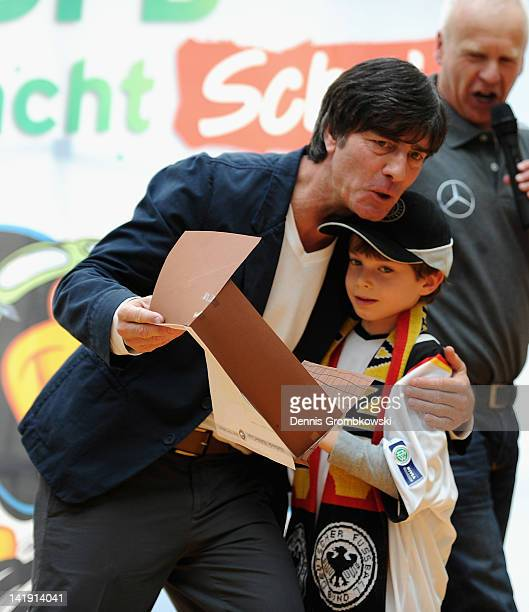 Head coach of the german national football team Joachim Loew hugs a young student during a school visit at Schillerschule on March 26 2012 in...