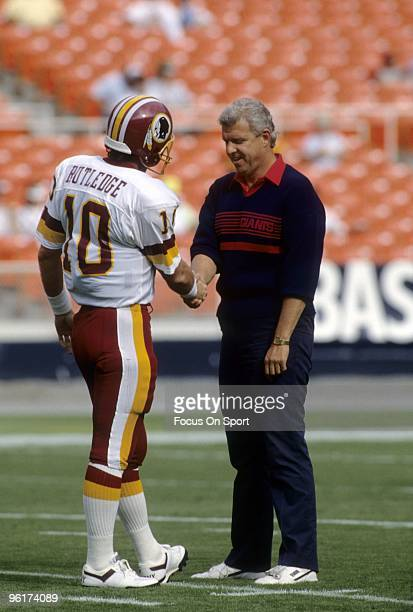 Head coach of the New York Giants Bill Parcells shakes hands with Washington Redskins quarterback Jeff Rutledge before a circa 1990 NFL football game...