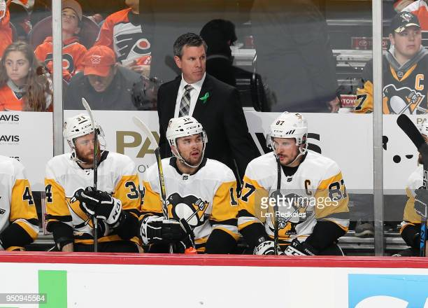 Head Coach of the Pittsburgh Penguins Mike Sullivan looks on during the first period behind Tom Kuhnhackl Dominik Simon and Sidney Crosby against the...