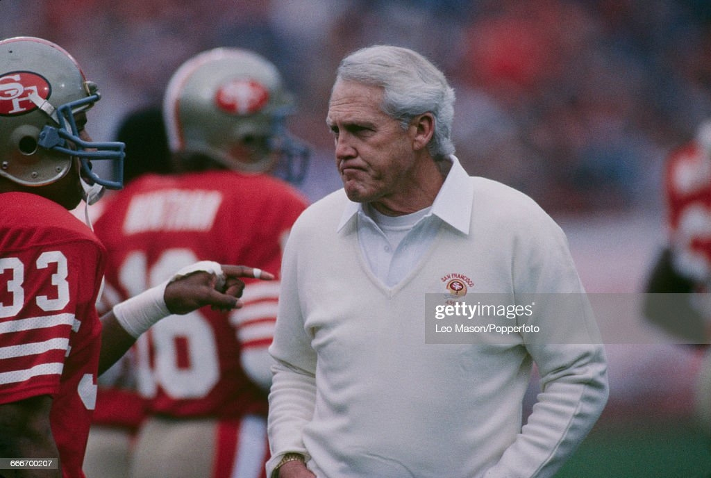 Head coach of the San Francisco 49ers, Bill Walsh (1931-2007) discusses tactics with running back Roger Craig (#33) during Super Bowl XIX at Stanford Stadium in California, United States on 20th January 1985. The San Francisco 49ers would go on to win the Super Bowl 38 - 16.