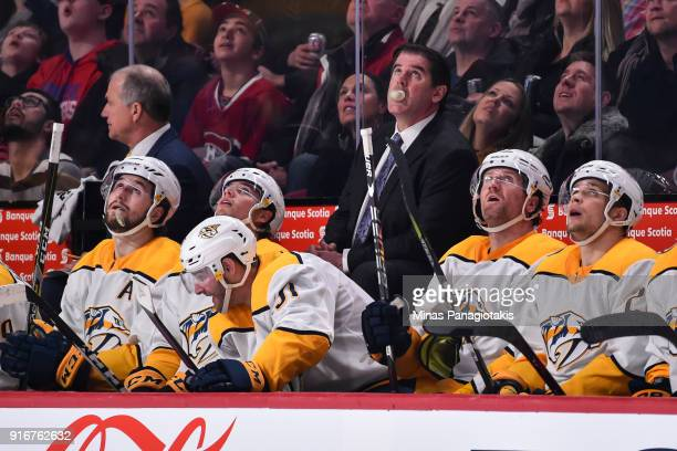 Head coach of the the Nashville Predators Peter Laviolette blows a bubble while chewing gum against the Montreal Canadiens during the NHL game at the...