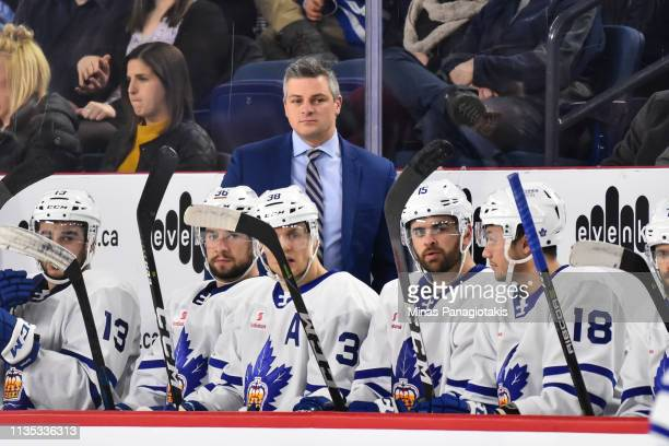 Head coach of the Toronto Marlies Sheldon Keefe looks on from behind the bench against the Laval Rocket during the AHL game at Place Bell on March 8,...