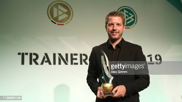 Head coach of Werder Bremen Florian Kohfeldt poses for a picture with his trophy after being awarded as the head coach of the year 2018 at the Hyatt...